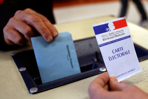 A man casts his vote in the ballot box in a polling in Montpellier as France goes to the polls in the first round of regional elections
