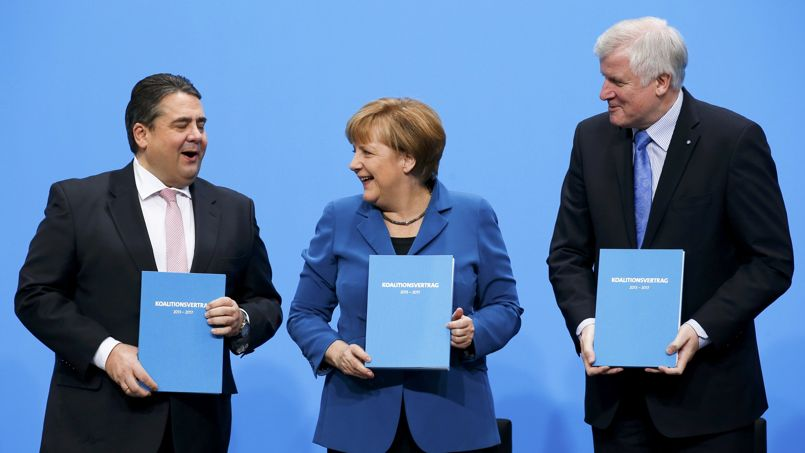 German Chancellor Merkel, leader of the CDU, Seehofer leader of the CSU and Gabriel leader of the SPD hold copies of a signed coalition treaty during a ceremony in Berlin
